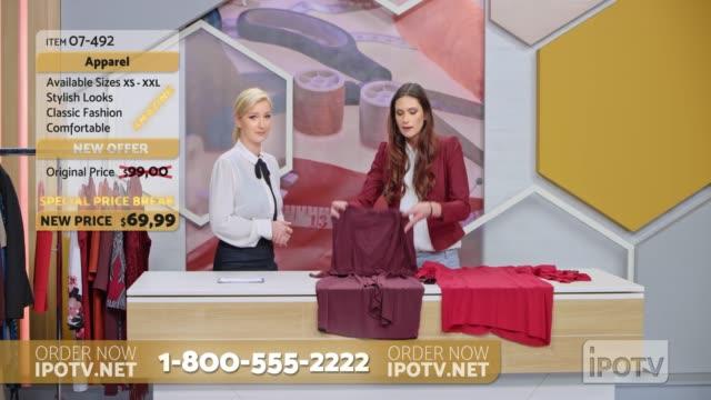 us-infomercial montage: weiblicher stylist auf einer tv-show im gespräch mit der gastgeberin über die entwürfe der kleider auf dem tisch - moderator stock-videos und b-roll-filmmaterial