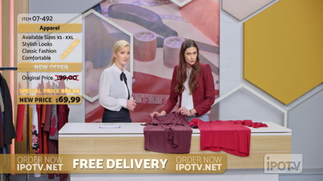 us infomercial montage: female stylist on a tv show talking to the female host about the designs of the dresses on the table - strategia di vendita video stock e b–roll