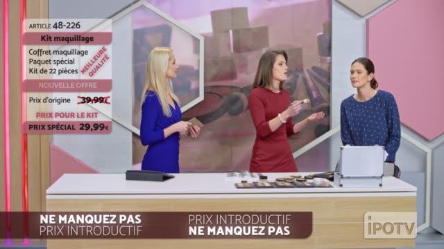 フランス語でインフォマーシャルモンタージュ: 女性はメイクアップブラシを提示し、女性モデルの使用を実証しながら女性ホストと話すアーティストをメイクアップ - フェイスブラシ点の映像素材/bロール