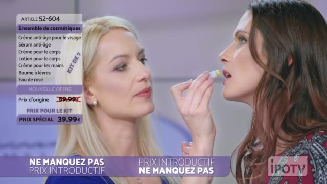 infomercial montage in french: woman presenting a lip salve from the cosmetic line on an infomercial show putting some on the female model's lips while talking to the female host - television host stock videos & royalty-free footage