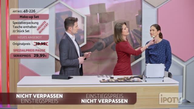 infomercial montage auf deutsch: weibliche make-up-künstlerin demonstriert den einsatz des make-up-pinsel auf der infomercial show - fernsehwerbung stock-videos und b-roll-filmmaterial