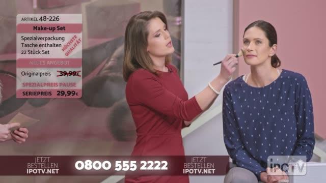 ドイツ語でインフォマーシャルモンタージュ: 女性はメイクアップブラシを提示し、女性モデルでの使用を実証しながら、女性ホストと話すアーティストをメイクアップ - フェイスブラシ点の映像素材/bロール