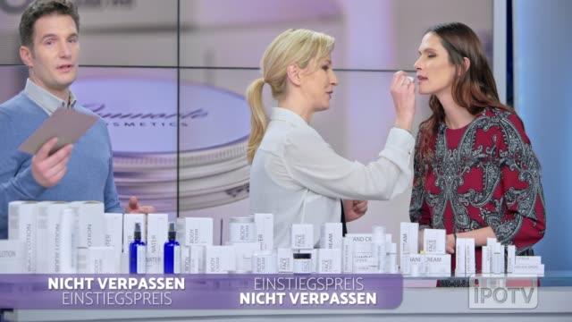 infomercial montage auf deutsch: frau platziert einige lippensalve der kosmetiklinie, die sie auf den lippen des weiblichen models präsentiert, während sie mit dem männlichen wirt der infomercial show spricht - fernsehwerbung stock-videos und b-roll-filmmaterial