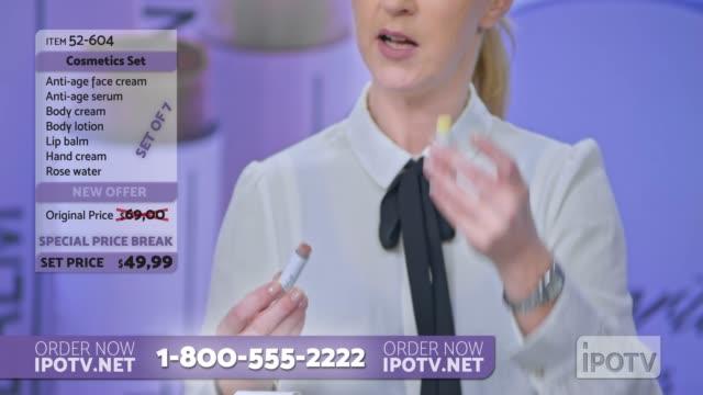 us-infomercial montage: frau platziert einige lippensalve der kosmetiklinie, die sie auf den lippen des weiblichen models präsentiert, während sie mit dem männlichen wirt der infomercial show spricht - pullover stock-videos und b-roll-filmmaterial