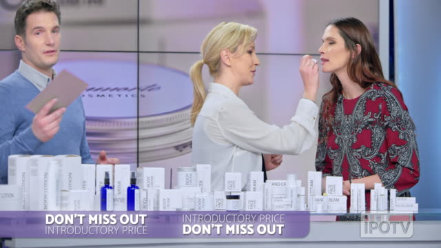 uk infomercial montage: woman placing some lip salve of the cosmetic line she is presenting on the female model's lips while talking to the male host of the infomercial show - television show stock videos & royalty-free footage