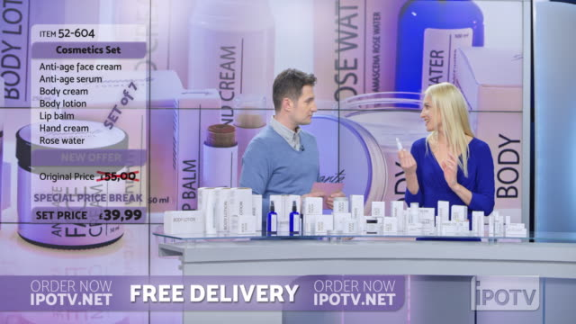 uk infomercial montage: woman presenting a cosmetic line on an infomercial show placing the product onto the male host's hand as they talk - television show stock videos & royalty-free footage