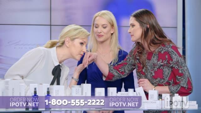 us-infomercial montage: frau präsentiert eine kosmetische linie auf einer infomercial show reibung sahne auf die hand eines weiblichen model, während im gespräch mit der weiblichen gastgeberin - fernsehwerbung stock-videos und b-roll-filmmaterial
