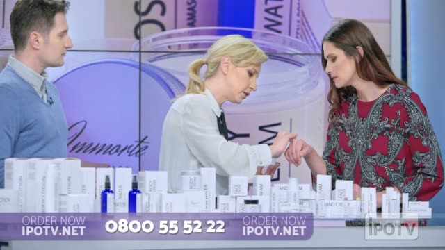 uk infomercial montage: woman presenting a cosmetic line on an infomercial show rubbing some cream on the female model while talking to the male host and explaining the product - television host stock videos & royalty-free footage