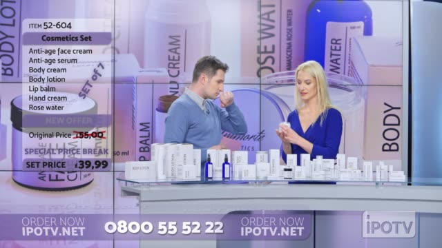 uk infomercial montage: woman presenting a cosmetic line on an infomercial show rubbing some cream onto the back of the male host's hand as they talk - television advertisement stock videos & royalty-free footage