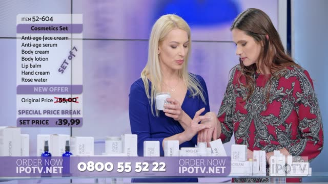 UK infomercial montage: Woman presenting a cosmetic line on an infomercial show rubbing cream onto the hand of a female model while talking to the female host