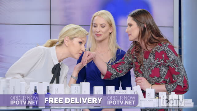 uk infomercial montage: woman presenting a cosmetic line on an infomercial show rubbing cream onto the hand of a female model while talking to the female host - strategia di vendita video stock e b–roll