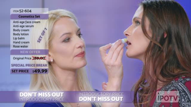 us infomercial montage: woman presenting a lip salve from the cosmetic line on an infomercial show putting some on the female model's lips while talking to the female host - strategia di vendita video stock e b–roll