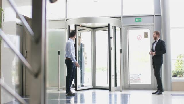 informal business meeting in office building lobby - revolving door stock videos & royalty-free footage