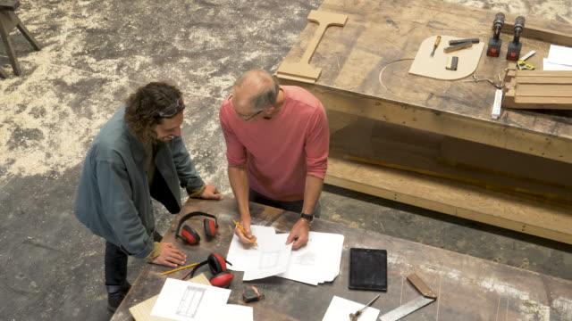 informal meeting of workers in a furniture factory - 作業場点の映像素材/bロール