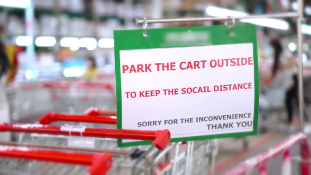 stockvideo's en b-roll-footage met informatiebord de kar buiten voor sociale distantiëring bij de supermarkt tijdens covid-19 pandemie. - heropening