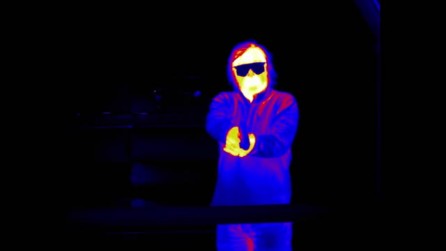 Infrared thermal imaging of a man firing a hand gun