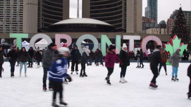 inhabitants people of toronto city skate in nathan phillips square in winter, canada - 文字点の映像素材/bロール