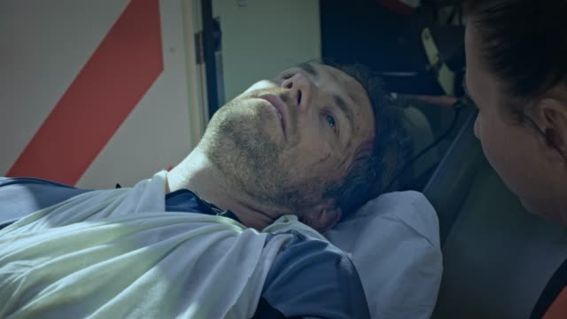 injured caucasian male cyclist being loaded into the ambulance on a stretcher - stretcher stock videos & royalty-free footage