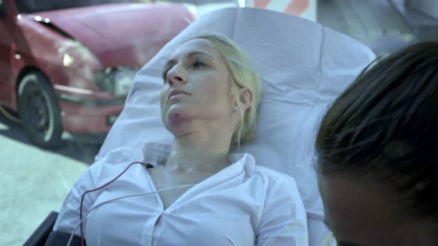 injured caucasian woman lying on the stretcher and being taken care of by the paramedic team after the car accident - injured stock videos & royalty-free footage