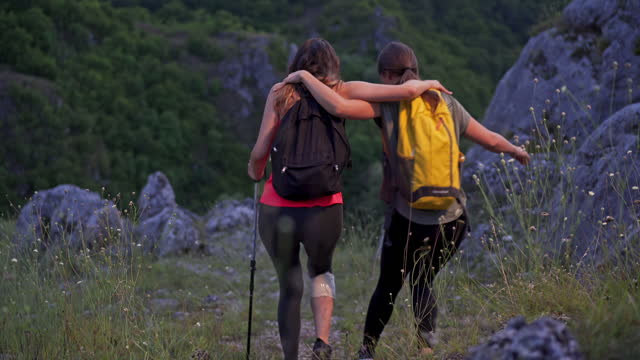 injured female hiker, using hiking pole as a support while trying to walk down the hiking route, while her friend also helping her - misfortune stock videos & royalty-free footage