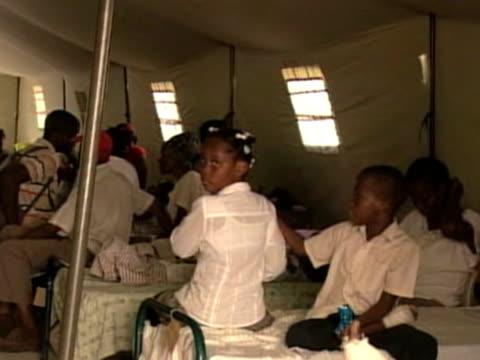 Injured Haitians wait for medical treatment at Cuban makeshift hospital following devastating earthquake Haiti 25 February 2010