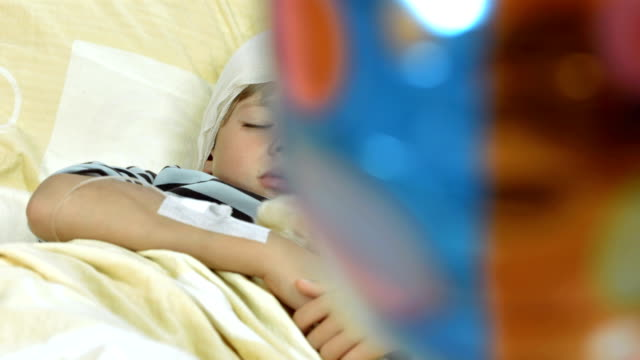 hd dolly: injured little boy sleeping in bed - teddy bear stock videos and b-roll footage