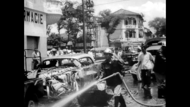 Injured man being escorted away from bomb site / fireman hosing down small fires and clean up beginning / CU destroyed cars and firefighters hosing...