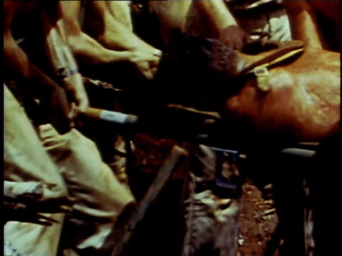 injured man laid on stretcher / men carrying stretcher through debris - 死傷者点の映像素材/bロール