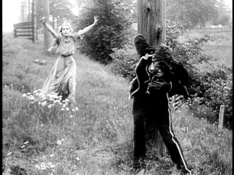 1910 B&W Injured man leaning against tree, woman running down hill with arms raised/ USA
