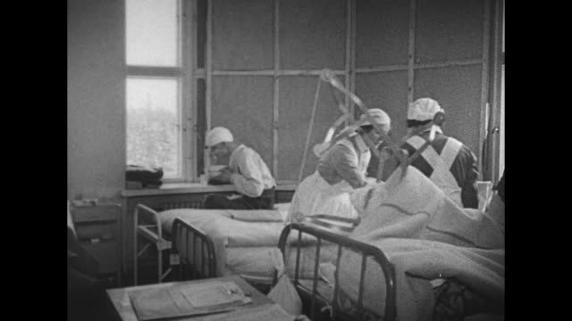 injured man on stretcher carried to hospital door by men with red cross nurses attending / vs doctors and nurses on ward floor / they work on... - world war ii stock videos & royalty-free footage