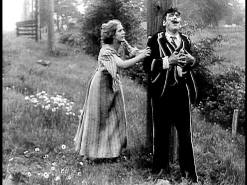 1910 b&w injured man throwing sack with money towards woman and falling on ground/ usa - 1910 stock-videos und b-roll-filmmaterial