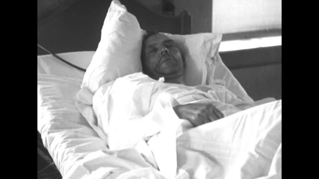 stockvideo's en b-roll-footage met injured man wrapped in bandages in hospital bed / man with arm injury drinks from small glass - drinking health 1930 film