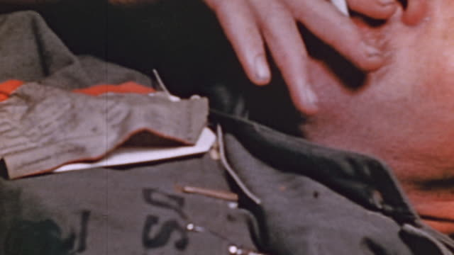 vídeos de stock, filmes e b-roll de cu injured marine smoking while undergoing treatment in the wardroom of the uss lubbock and another soldier with an iv slumped over transfer tags... - crachá