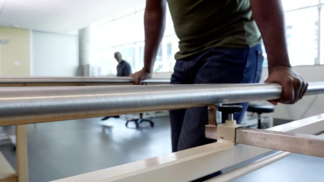 injured military veteran uses parallel bars for assistance in walking in rehabilitation center - recovery stock videos & royalty-free footage