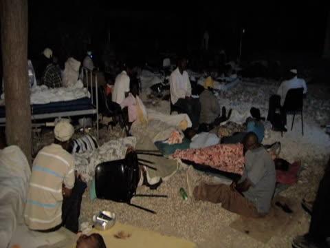 vídeos de stock e filmes b-roll de injured people lay on floor of hospital grounds at night as they wait for treatment following devastating earthquake haiti 14 january 2010 - hispaniola
