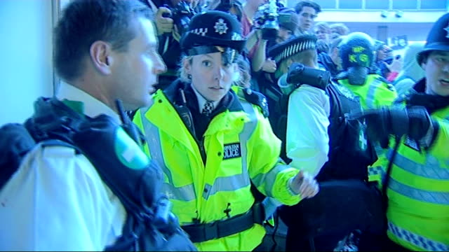 Injured police officer in riot gear helped from scene and policewoman with tape covering gash on face helped along by colleague Group of protestors...