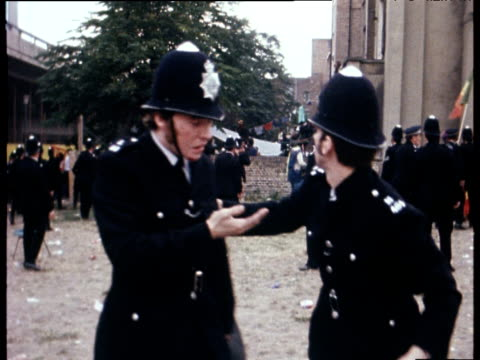 Injured police officer is led away by colleague during disturbances at Notting Hill Carnival London Aug 76