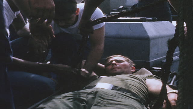 vídeos y material grabado en eventos de stock de injured soldier lying on deck of pbr, soldiers around him, and being helped up from the deck / vietnam - víctima de accidente