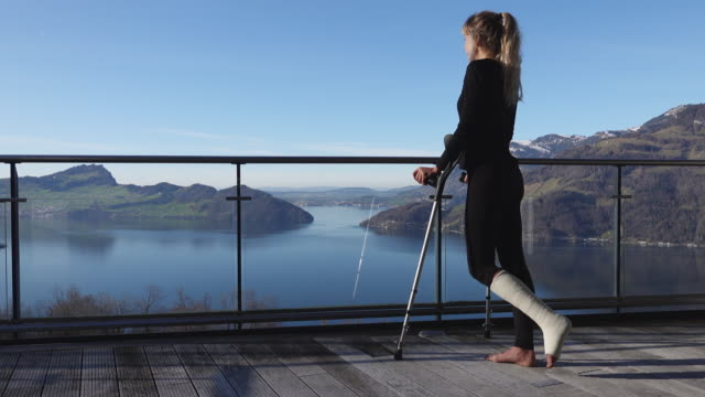 injured woman uses crutches to walk across balcony, view over lake - crutch stock videos & royalty-free footage