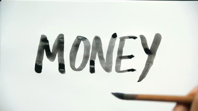 "stockvideo's en b-roll-footage met ink brush writing word, "" money"" - westers schrift"