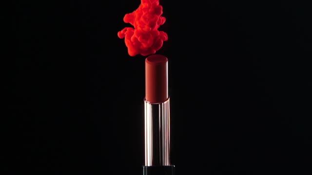 vidéos et rushes de chute d'encre tombant au rouge à lèvres avec le fond noir au mouvement lent - red