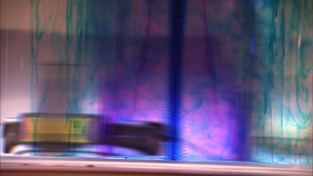 vídeos de stock e filmes b-roll de inks of different colors streak the inside of a spinning tornado machine. - universidade de washington