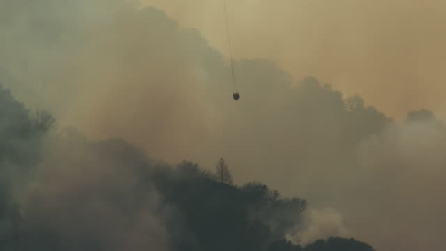 inland empire, ca, u.s. - helicopter carrying water buckets over burning forests, on tuesday, august 4, 2020. coronavirus fears complicate apple fire... - forest stock videos & royalty-free footage