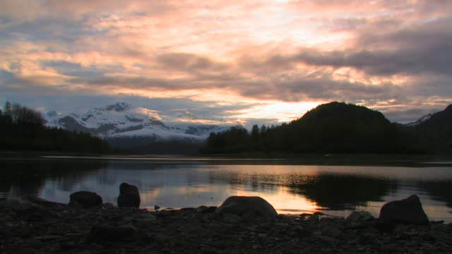 ws, inlet with forest and snow capped mountains in background at sunset, glacier bay national park and preserve, alaska, usa - inlet stock videos & royalty-free footage