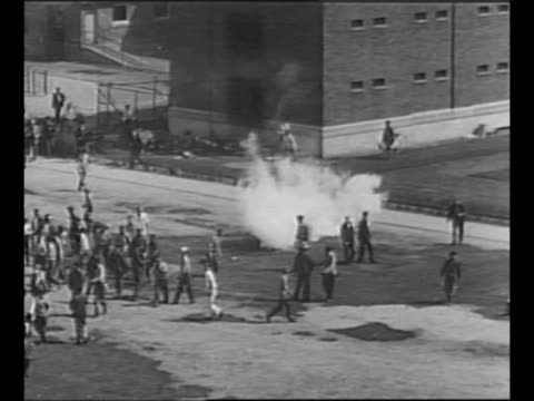 inmates mill about on prison grounds during michigan state prison riot some in foreground start to smash something / side view man shoots tear gas... - prison window stock videos & royalty-free footage