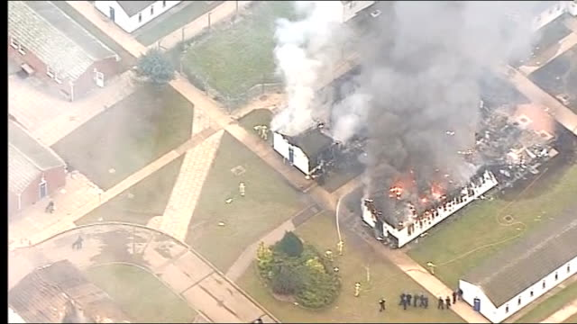 aerials of prison buildings burning england sussex arundel ford open prison ext aerials burning prison buildings clouds of smoke firefighters trying... - prison riot stock videos & royalty-free footage