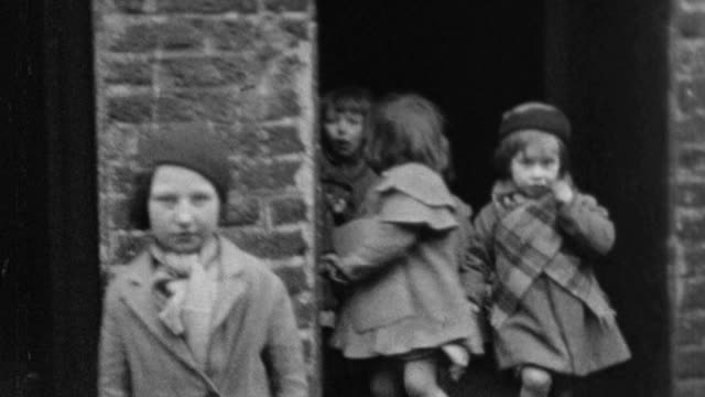 1937 montage inner city mothers and their children on stoops, sidewalks, and streets in tenement slum area, showing the poor condition of some children / london, england, united kingdom - povertà video stock e b–roll