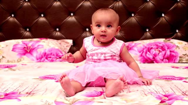 oskyldig 6 månader gammal flicka som spelar på sängen hemma - endast en flickbaby bildbanksvideor och videomaterial från bakom kulisserna