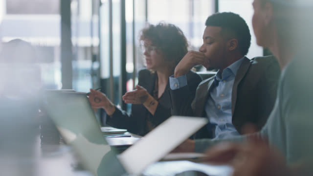 innovative diverse business partners converse and collaborate with each other during a busy team business meeting - business stock videos & royalty-free footage