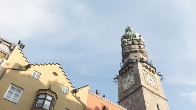 innsbruck, österreich, schöner palast und uhrenturm mit baumvordergrund in innsbruck österreich - kirche stock-videos und b-roll-filmmaterial
